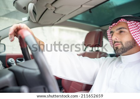 Arabic young businessman driving car - stock photo