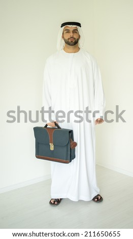 Arabic young businessman posing with bag - stock photo