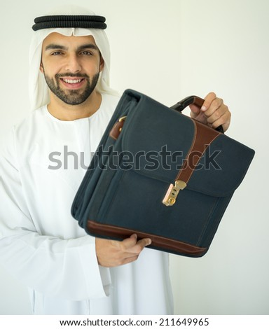 Arabic young businessman wtih briefcase - stock photo