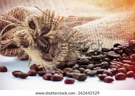 Arabica coffee beans and small sack on blue background. Post processed with vintage filter.  - stock photo