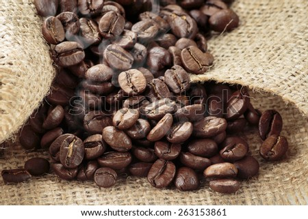 Arabica coffee beans on burlap background. Post processed with smoke brush.