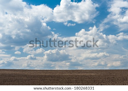 Arable land and cloudy sky - stock photo