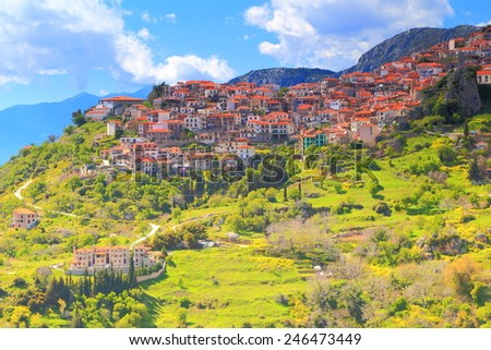 Arachova village with distant houses spread on green slopes of Parnassus Mountains, Greece - stock photo