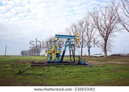 ARAD, ROMANIA - FRIDAY, DECEMBER 5, 2014: A pumpjack pumps oil out of the ground at a production field operated by OMV Petrom S.A, the largest gas and oil producer in Eastern Europe  - stock photo