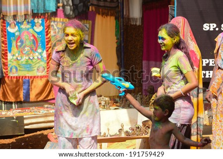 ARAMBOL, GOA - MARCH 17: Unidentified people celebrate Holi festival in Arambol Main Street, GOA, India on March 17, 2014. It's a religious spring holiday and also known as Festival of Colours. - stock photo