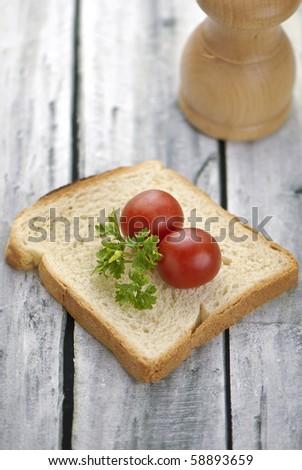 Aranged food two tomatoe on toast, on wooden background - stock photo