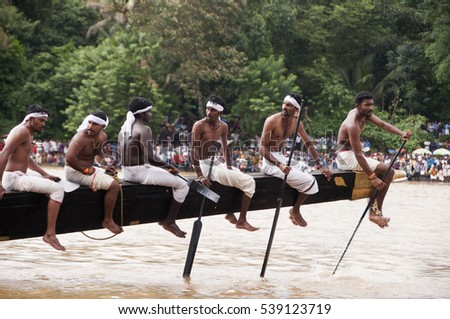 ARANMULA, KERALA, INDIA - 20 SEPTEMBER 2013 : Oarsmen of a team wearing traditional dress participate at the Aranmula Boat race, This Boat Race is the oldest river boat fiesta in Kerala.