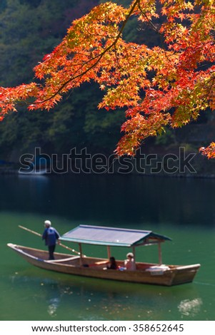 Arashiyama, red maple leaves blooming at Arashiyama in Autumn with tourists in a sightseeing boat service rowing in Katsura river with nice scenery, Kyoto, Japan - stock photo