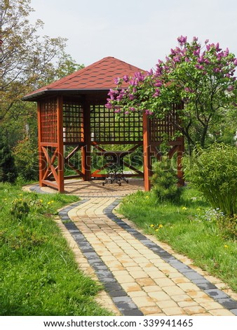 Arbor in garden with lilac vertical - stock photo