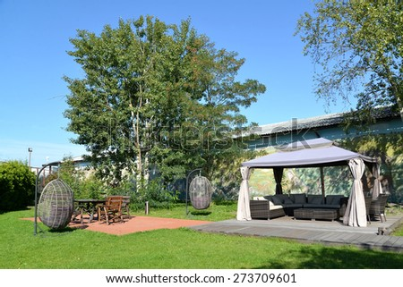 Arbor tent, hanging chairs and wooden garden furniture in the territory of the center of rest, Kaliningrad - stock photo