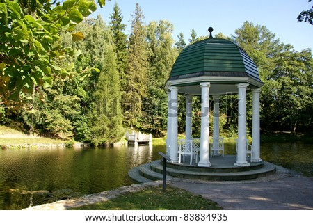 Arbour on a background of a pond and trees