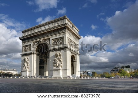 Arc de Triomphe in Paris France with dramatic clouds and blue sky - stock photo