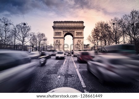 Arc-de-Triomphe on the Champs-Elysees in Paris, France, at sunset. Heavy traffic on the avenue. - stock photo