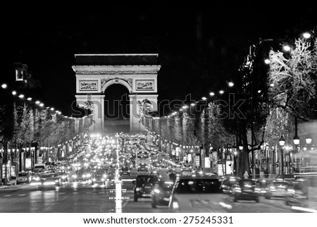 Arc de Triomphe, Paris. Illuminated avenue Champs Elysees by night. Cars traffic.