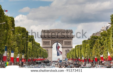 Arc de Triomphe viewed up the Champs Elysees and a large french flag flying under the arch - stock photo