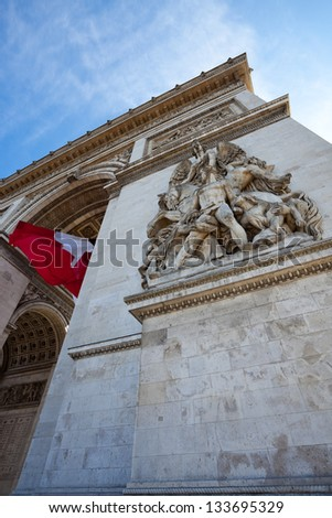 Arc de Triomphe with French flag hanging from vaulted ceiling inside the arch. - stock photo