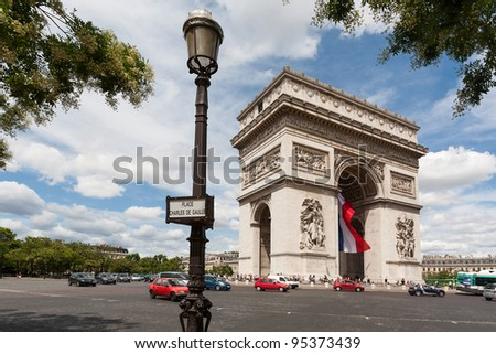 Arc de Triomphe with lamppost in foreground showing the full roundabout - stock photo