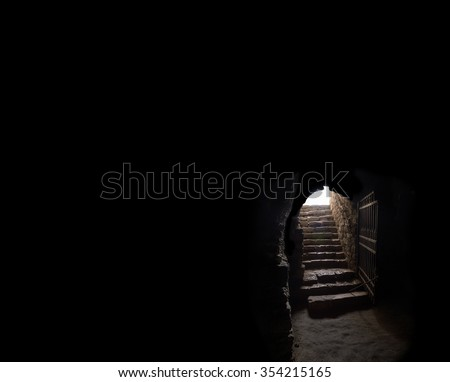 Arc fort passageway from cold damp Blackness to glow Light with rusted iron grate cell. Gaol rugged ominous shadow solid hallway with upward leading to day sunlight with space for text on sky backdrop - stock photo