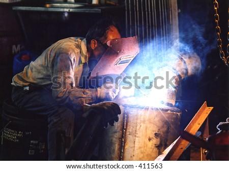 Arc welder in the midst of work - stock photo