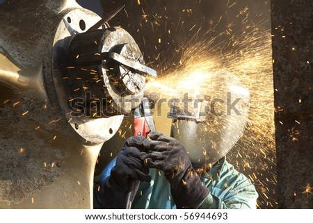 arc welder working on a tug boat wheel
