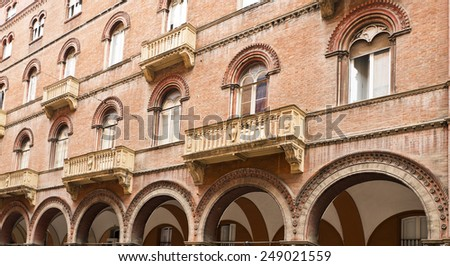 Arcade, windows and balconies on an elegant building in Bologna, Italy - stock photo