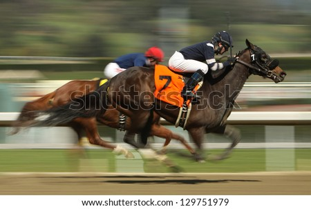 "ARCADIA, CA - FEBRUARY 23: Jockey Tyler Baze pilots ""Night Teller"" to a 3rd place finish in a maiden race at Santa Anita Park on February 23, 2013 in Arcadia, CA. - stock photo"