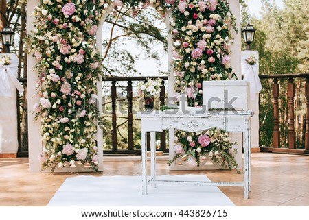 arch for the wedding ceremony, decorated with fresh flowers  in a pine forest