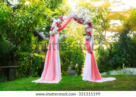 Arch for the wedding ceremony in the tropical garden. Floristic composition in pink.