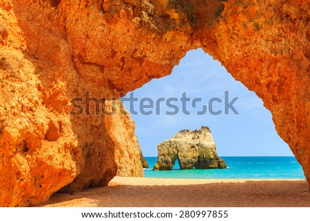 Arch of a cliff rock on Alvor beach and view of sea, Portugal - stock photo
