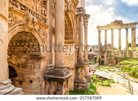 Arch of Emperor Septimius Severus and Temple of Saturn in the distance at the Roman Forum in Rome, Italy - stock photo