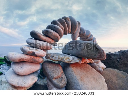 Arch of pebbles between of the stones on the coast - stock photo
