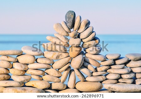 Arch of pebbles between of the stones on the seashore - stock photo