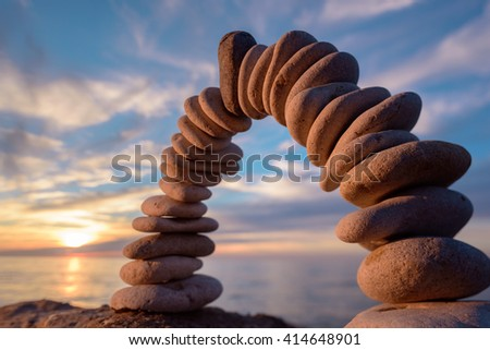 Arch of pebbles on sea background - stock photo