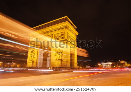 Arch of Triumph of the Star (Arc de Triomphe de l'Etoile) in Paris (France) at night. Trail of traffic lights in the foreground. - stock photo