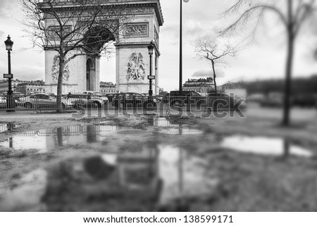 Arch of Triumph on Place de l'Etoile in Paris, France, reflecting in a big puddle on the sidewalk - stock photo