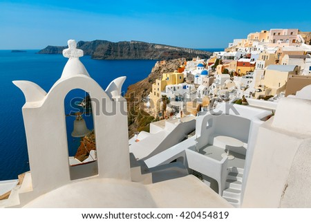 Arch with a bell, white houses and church with blue domes in Oia or Ia, island Santorini, Greece - stock photo