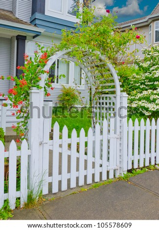 Arch wooden entrance with the fence, wreathed with flowers - stock photo