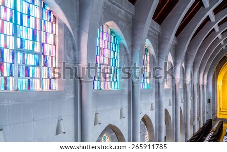 Arched columns in monastery chapel with stained glass windows - stock photo