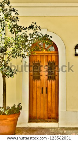 Arched doorway with ornate door and iron bars - stock photo