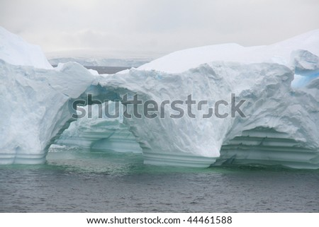 Arched formations in iceberg floating offshore,   Erreras Channel,  Antarctica - stock photo