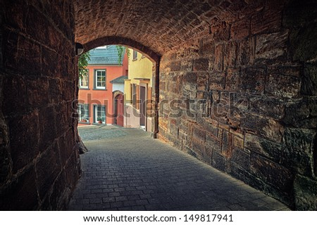 Arched pedestrian tunnel in small European city  - stock photo