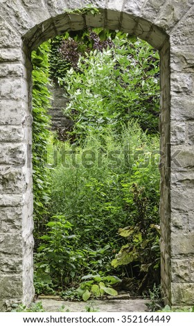 Arched stone entranceway to green garden nook on college campus in summer, for themes of tradition, growth, exploration and education - stock photo