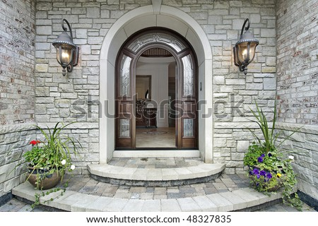 Arched stone entry of luxury suburban home - stock photo