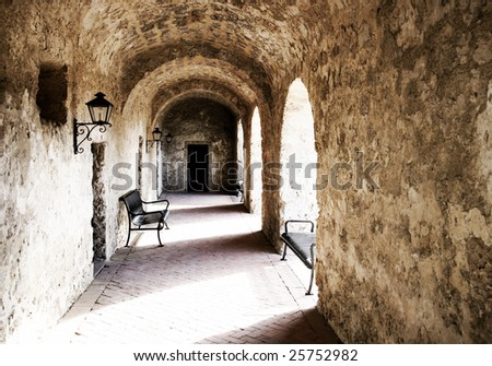 Arched stone walkway with high contrast light and shadow, leading to a doorway (authentic 18th century Spanish Mission architecture). - stock photo