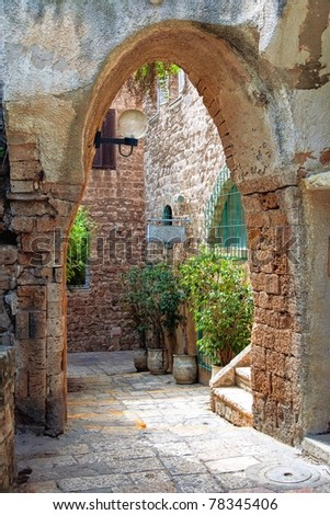 Arched street in mediterranean town - stock photo