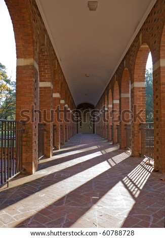 Arched walkway on the campus of the College of William and Mary in Williamsburg, Virginia, with slanting rays of the morning sun vertical - stock photo