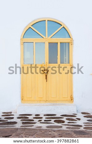 Arched wooden yellow door on the whitewashed building. - stock photo