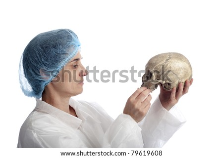 archeology female researcher inspecting a skull. Isolated on white background - stock photo