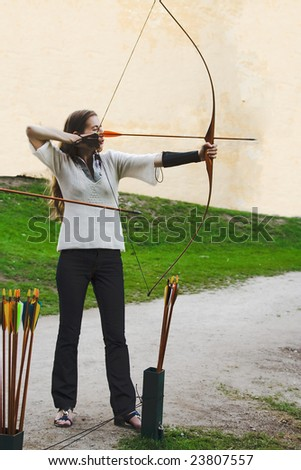 archer beauty girl plays arrow bow shooting sport stay side view position concentration