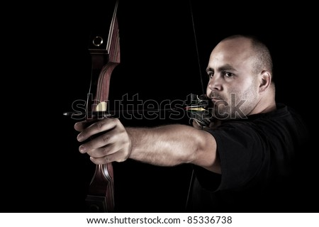 Archer in black on black background aiming with bow and arrow, with focus on bow. - stock photo